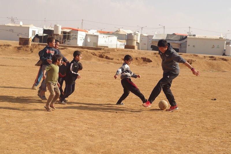 訪問先で子どもたちとサッカーをするカズさん